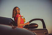 Cheerful young woman watching sunset while taking a break from driving