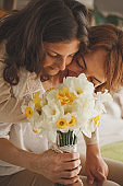 Mother and daughter enjoying scent of freshly picked daffodils