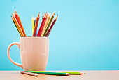 White mug full of brightly colored pencil crayons