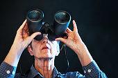 Senior woman peering through binoculars intently