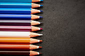 Multicolored pencil crayons in close-up by blank chalkboard