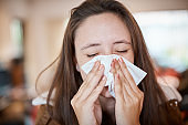 Young woman with cold or flu blows her nose on a tissue