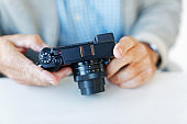 Male hands hold an unbranded camera