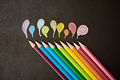 Nine colored pencils drawing little droplets on black
