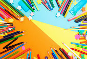 Variety of pens and pencils surround copy space on paper