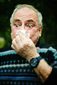 Senior man's eyes bug out as he blows his nose on a tissue