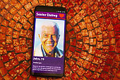 Mobile phone screen displays an old man on an internet dating site