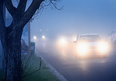 Commuters' cars drive through fog on city street at twilight with headlights on