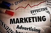 Newspaper headlines about effective marketing and advertising, with rising graph