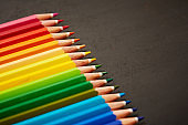 Multicolored pencil crayons at an angle by blank chalkboard