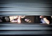 Worried senior woman peers through blinds