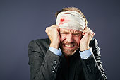 Businessman with bandages head is in extreme pain