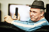 Angry old man holds TV remote control