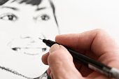 Man's hand drawing a pen-and-ink sketch of a beautiful woman's face
