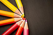 Seven colored pencils in semi-circle on black