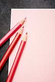 Three red crayons on blank pink notepad