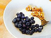 Close-up healthy breakfast of blueberries, yogurt and walnuts