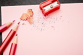 Three red pencils and a sharpener on pink notepad
