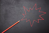 Red colored pencil draws zigzag thought bubble on chalkboard