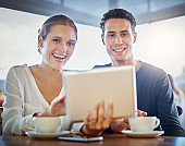 Smiling young couple in cafe look up from digital tablet