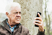 Senior man in forest looks at mobile phone, irritated