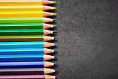 Multicolored pencil crayons line up by blank chalkboard