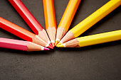 Colored pencils form red, orange, and yellow semicircle on black
