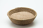 Sesame seeds in weave wicker basket isolated
