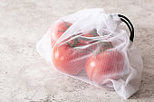 tomato vegetables in reusable mesh nylon bag, plastic free zero waste concept