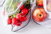 fruits and vegetables radish apple in reusable mesh nylon bag, plastic free zero waste concept