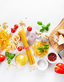 ingredients for italian cousine flat lay, pasta spaghetti penne fusilli tomato oil vegetables