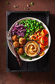 healthy vegan lunch bowl with falafel hummus carrot ribbons cabbage and peas