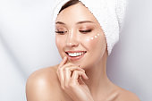 pretty girl with towel on her head and cream on the cheek holding her arm near mouth and smiling
