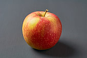 Single red fresh whole ripe apple full of vitamins lies on old dark scratched concrete table on kitchen. Harvest or diet concept. Close-up