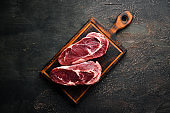 Raw marbled meat Black Angus Steak Ribeye. At the aged table. Top view. Free space for your text.