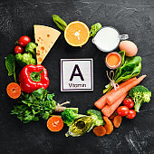 Foods containing natural Vitamin A: broccoli, carrots, milk, cheese, spinach, apricots, parsley, tomatoes. On a black stone kitchen background. Top view.