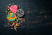 Caramel candies and lollipops. Colored candies. On a black background. Top view. free copying space.