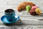 One full blue ceramic cup of fresh black coffee near whole baked croissant and various macaroons on old white rustic wooden table
