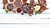 Cocoa beans, chocolate, cocoa butter and cocoa powder on a white wooden background. Top view. Free copy space.
