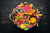 Colorful candies, jelly and marmalade in a wooden box. Sweets. On the old background. Top view. free copy space.