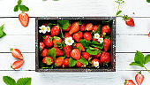 Fresh strawberries in a wooden box. Berries Top view. Free space for your text.