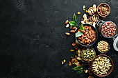 Assorted nuts on the old black background. Top view. Free space for your text.