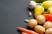 Set of different fresh whole ripe vegetables lies on dark concrete table. Copy space for text