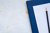 white desktop, green notebook lies on the table, pensil, with copy space, for advertisement