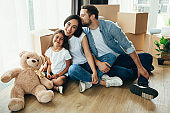 Pretty family moving home. Couple with child sitting on their new apartment with many carton boxes