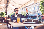 Young businessman waving to someone while talking on the phone during coffee break in a cafe