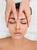 young woman getting head massaged at a beauty spa. Relax with head massage