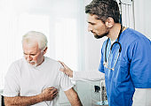 Senior patient suffering from heart attack . Doctor care about patient with heart pain