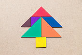 Color tangram in Pine or christmas tree shape on wood background