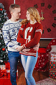 Young romantic cute couple staying at home and enjoying time together. Lovers hugging in cristmas decorated interior